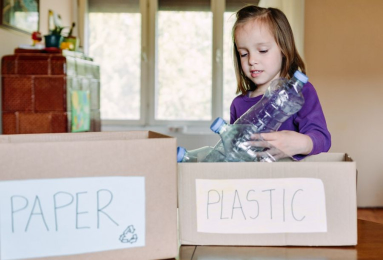Child girl putting plastic bottle in recycle box