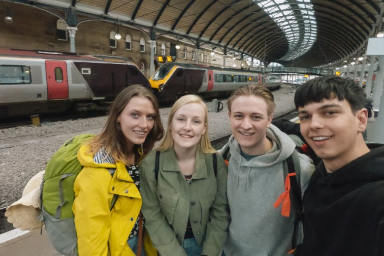 A group of four friends are standing side by side in a train station taking a selfie