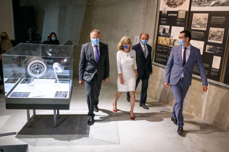 The director, the mayor, the ambassador and the minister go to the opening place of the exhibition.