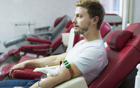 Men lying in a hospital giving a blooddonation-naslovna