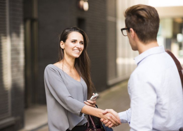 Young businessman and businesswoman shaking hands outside office