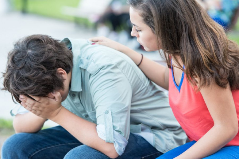 The teenage boy is crying with his hands in his face and the teenage girl is comforting him.